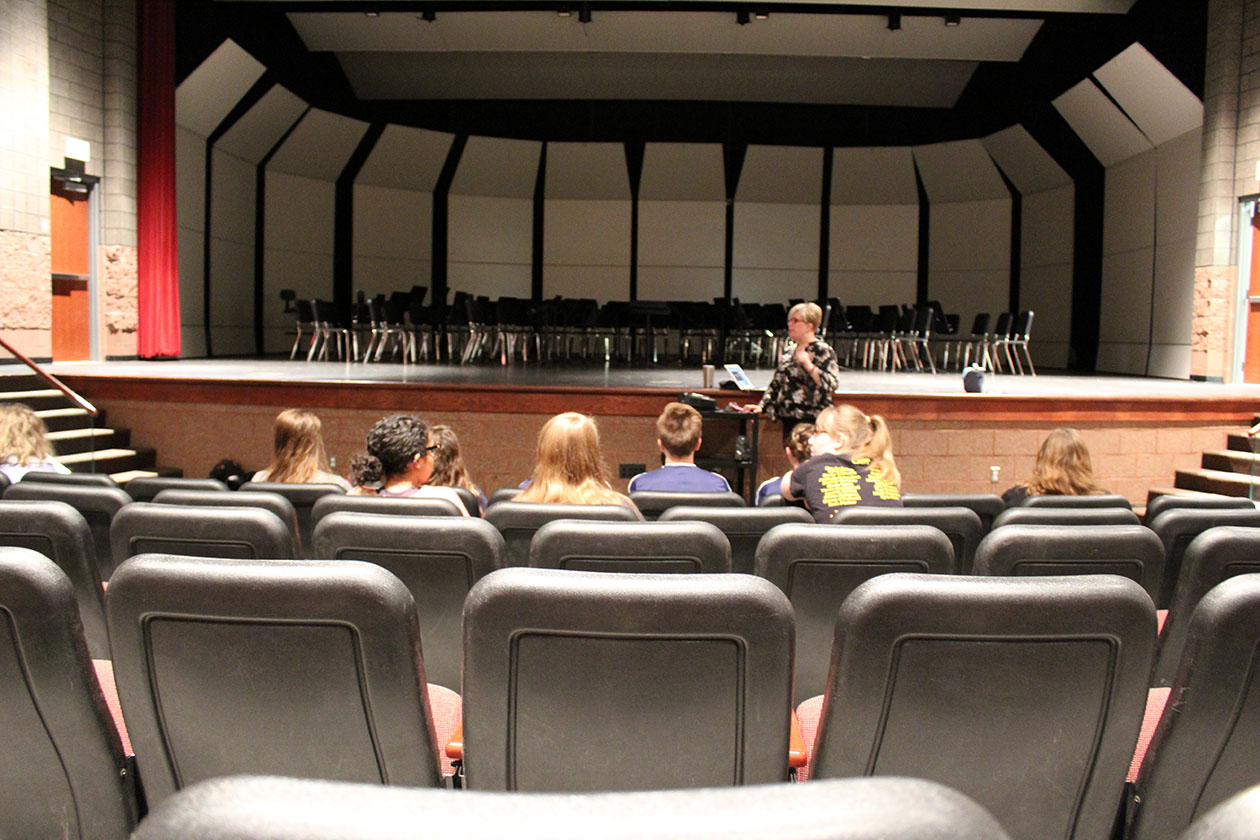 Choir students listen to director