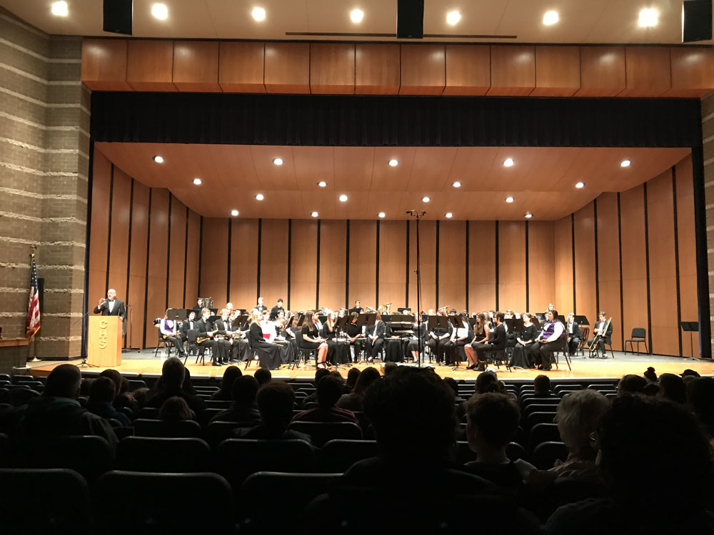 Full band performing in auditorium