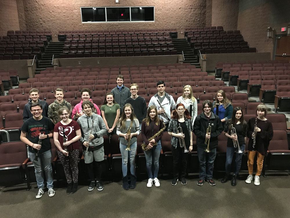 Students posing in auditorium with instruments