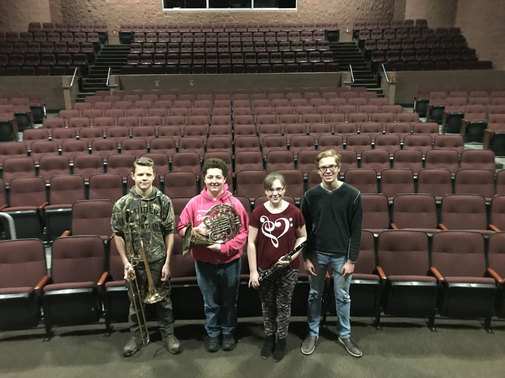 Four students with brass instruments