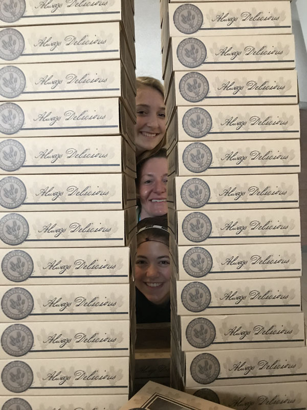 Students peeking through stacks of pies