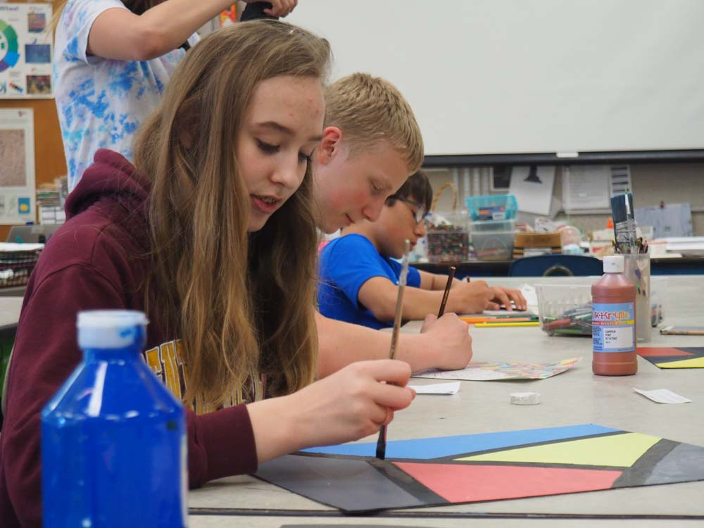 student working on art project and painting