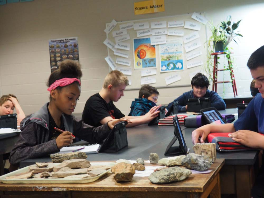students working in classroom on tablets