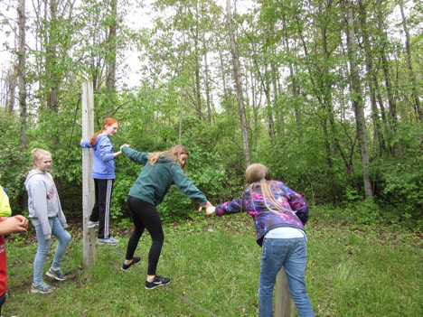 Students assisting each other in crossing wire