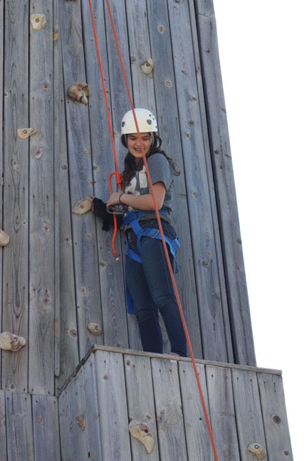 Student looking down from climbing wall