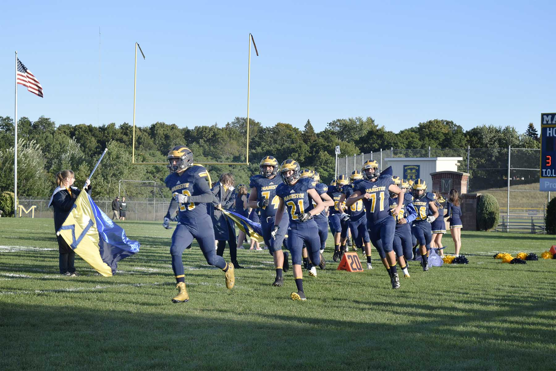 photo of Manistee high football team running on chippewa field