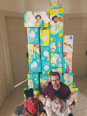 Teacher with young family in front of tower of diapers