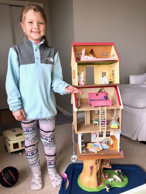 Girl next to doll house