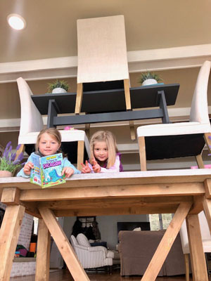Girls with books under furniture tower