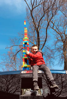 Boy on top of truck with lego tower