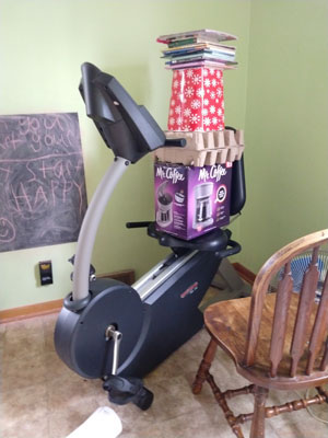 Tower of household items on exercise bike