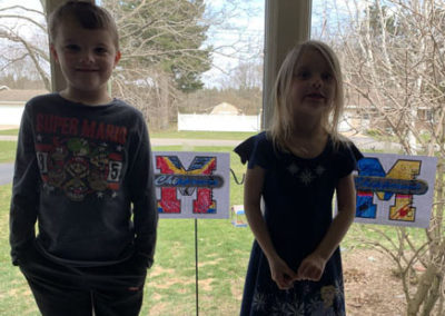Brother and sister displaying artwork