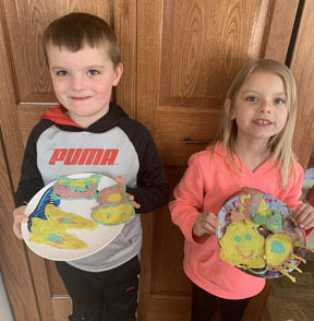 Boy and girl holding plate of pancake art