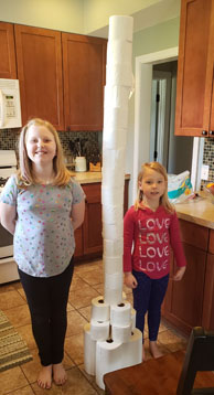 Girls standing next to toilet paper tower