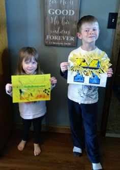 Brother and sister holding up artwork