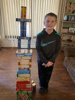 Boy next to tower of boxed foods