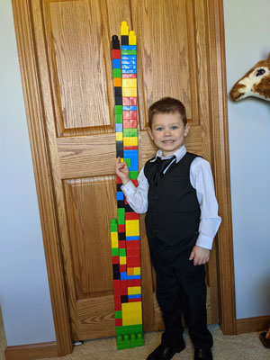 Boy standing next to lego tower