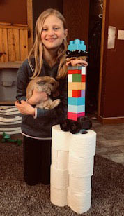 Girl holding rabbit next to tower of toilet paper and legos