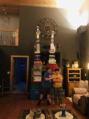 Boys standing next to twoo tall towers in living room