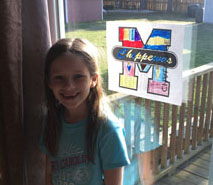 Girl in front of window displaying artwork