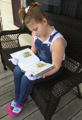 Girl reading book on bench