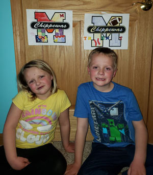 Brother and sister sitting in front of their art work