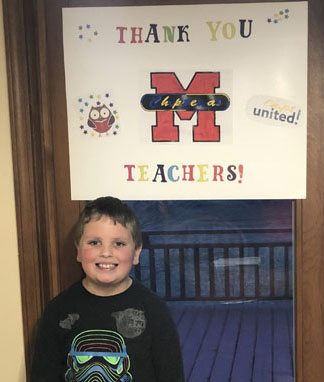 Boy smiling in front of thank you teachers sign