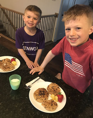 Brothers with plates of pancakes