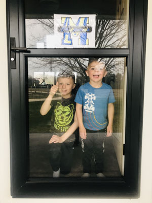 Brothers at front door displaying artwork