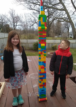 Brother and sister standing next to tower of Legos