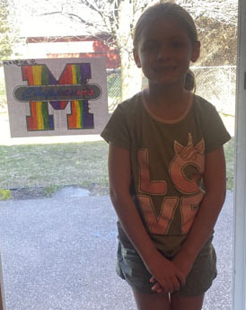 Girl standing in front of window displaying her artwork