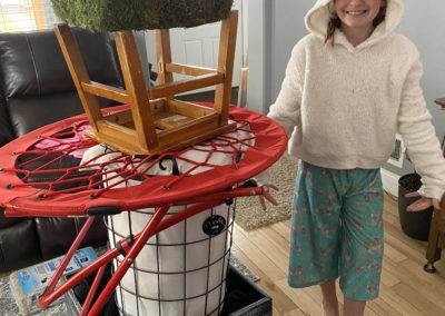 Girl next to tower of household items