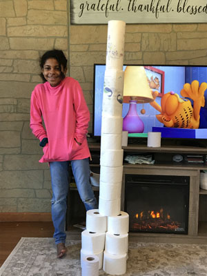 Girl next to tower of toilet paper