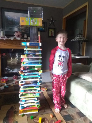 Boy next to tower of boxes