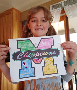 Girl holding up colored block M