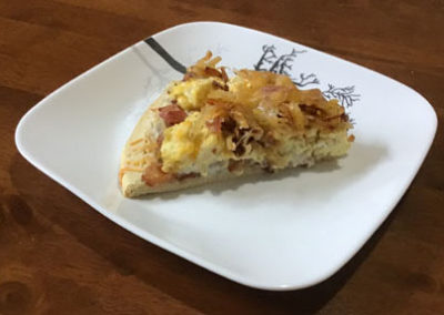 Plate with slice of breakfast pizza