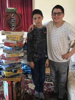 Two brothers standing next to tower of board games