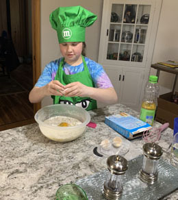 Girl in chef outfit making cupcakes