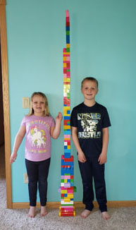 Boy and girl next to lego tower