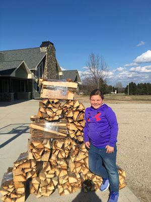Girl standing next to tower of firewood outdoors