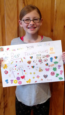 Girl with sign thanking teacher