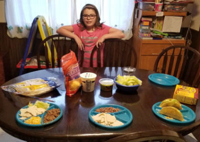 Girl standing next to dinner table