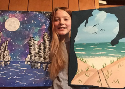Girl holing two paintings
