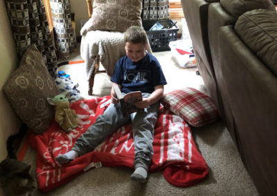 Boy reading in pillow fort